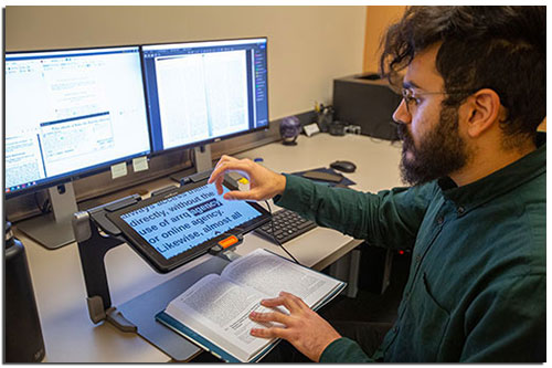 man at computer using screen reading technology to read