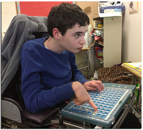 Young man in dark blue shirt sitting in wheelchair in front of computer using assistive technology